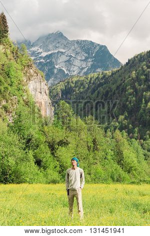 A Man Traveling On The Background Of Beautiful Mountain Scenery. Hiking Travel Lifestyle Concept.