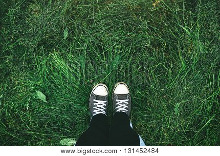 Young man standing in freshly mown grass lawn top view of casually dressed youth person in sneakers over mowed grassy field