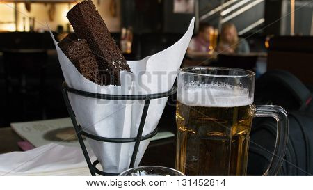 Croutons with beer in a glass on wooden background.
