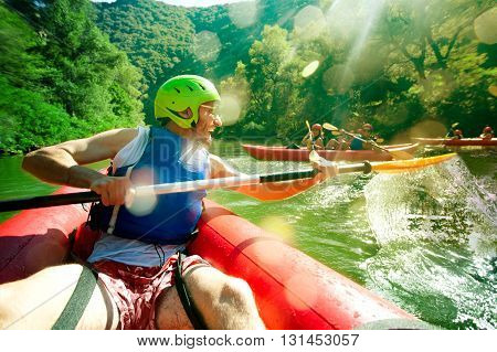 A young main in red inflatable canoe having fun splashing over his friends in a river.