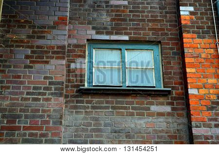 small window of an industrial building with brick wall