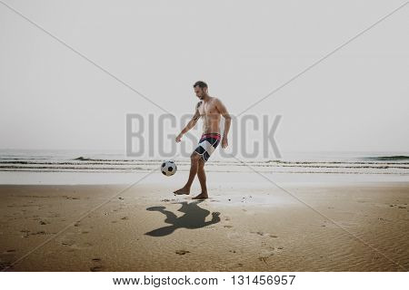 Handsome Man Playing Football Beach Concept