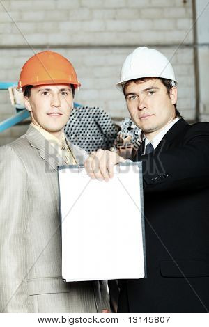 Industrial theme: two businessman working at a manufacturing area.