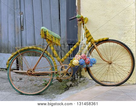 Vintage bicycle tied with thread and balls of woolen thread. The yard of the shop crafts. Grodno, Belarus.