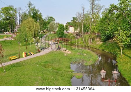 GRODNO, BELARUS - APRIL 5, 2016: The recreational area of the park Zhiliber in Grodno. The hills the river and walking people. Belarus.