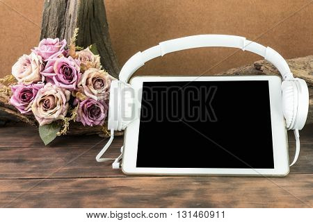 blank screen tablet with headphone on wooden table lifestyle and working concept