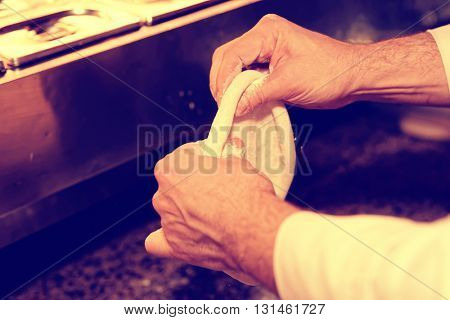 Chef is cooking pizza, forming dough, commercial kitchen, toned