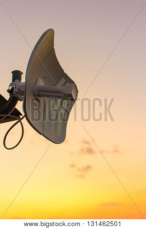 broadcasting antenna in the form of plate against the background of a beautiful sunset