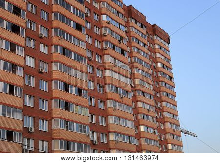 It stands tall building of orange brick for human habitation. blue sky