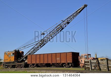 An old rusty crane with boom extended is ready to load a car on the railroad track.