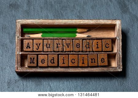 Ayurvedic medicine conceptual phrase. Textured wooden blocks with letters, green pencils in aged wood box. Gray stone background, macro