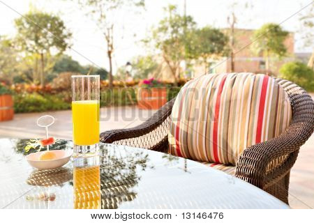 Glass Of Orange Juice And Ice Cream On Table In A Garden.