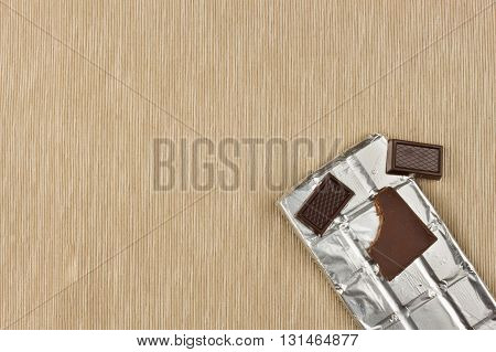 Chocolate wrapped in aluminum foil on bright tablecloth. Advertising on chocolate. Sales chocolate . Packing chocolate. Chocolate shop. Sweet chocolate bar.