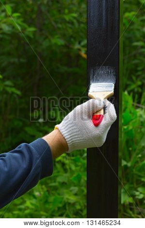 hand in glove rag paint brush steel post in black paint on a background of green foliage