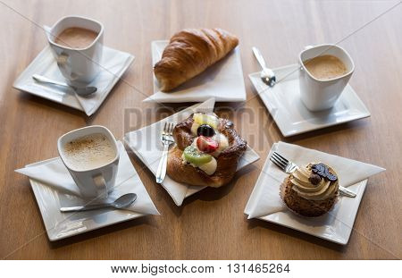 Still life. Three cups of coffee croissants and pastries. On a wooden table.