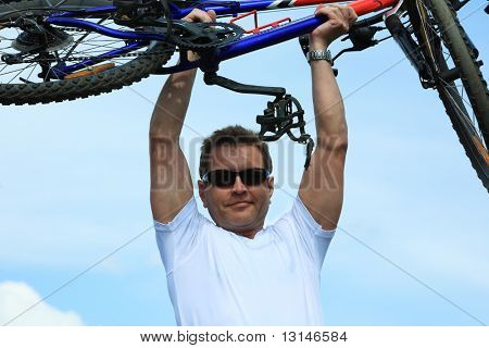 Sporty mature man cycling along cross country.