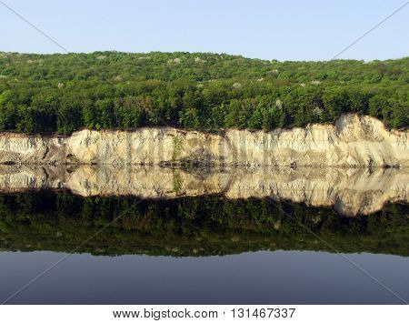 Mirroring the steep bank of the river Dnepr (mirror reflection).
