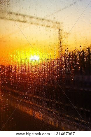 water drops on the glass of the train on the background of setting sun railroad