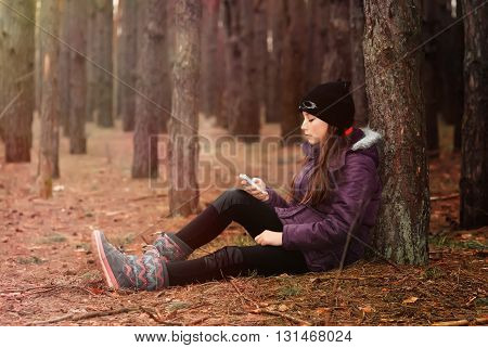 teenager girl sits in the autumn forest with a mobile phone