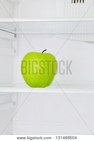 Lifestyle concept.Big green apple in domestic refrigerator taken closeup.Toned image.