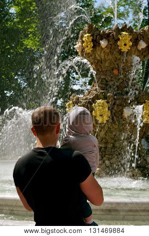 Russia.Saint-Petersburg.Beautiful show with fountains watching the child with dad.