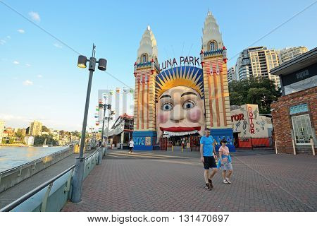 SYDNEY, AUSTRALIA - OCTOBER 19, 2015 - Unidentified couple passing by Luna Park entrance, Luna park is an amusement park located near Milsons Point in Sydney, Australia.