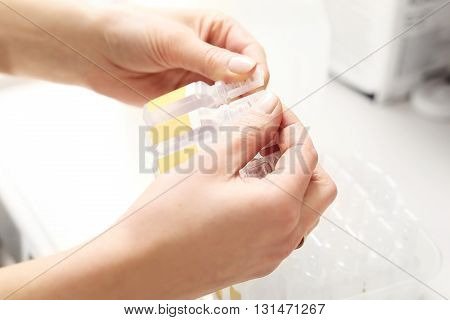 Hands nurse preparing an injection ampoules bursting drug