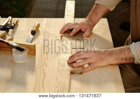 Carpenter at work arranging pieces of wood on table horizontal