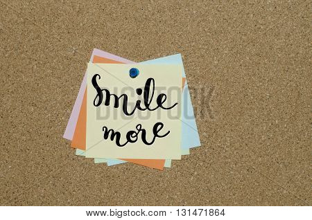 Smile more hand lettering text on paper note fixed on cork board