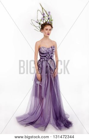 Full body shot of beautiful young woman in fashion elegant designer purple dress with crown on white blackground