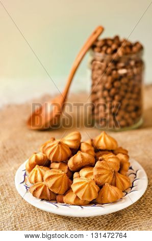 Small cookies on a plate and burlap. Bank with chocolate balls in the background and a wooden spoon, warm light and bokeh. A gradient background.