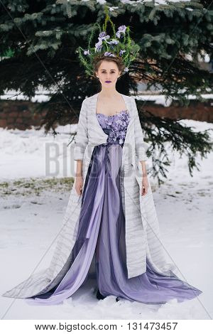 Outdoor full body shot of beautiful young woman in fashion elegant designer purple dress with crown in winter