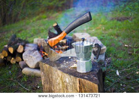 A Coffee Maker And An Axe Near A Fire.