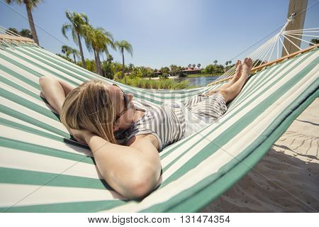 Woman sunbathing, relaxing and resting in a hammock while staying at a tropical resort on vacation