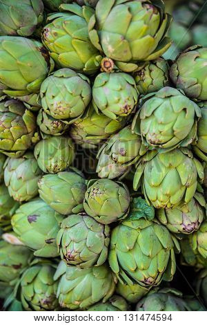Background of fresh green artichokes on market