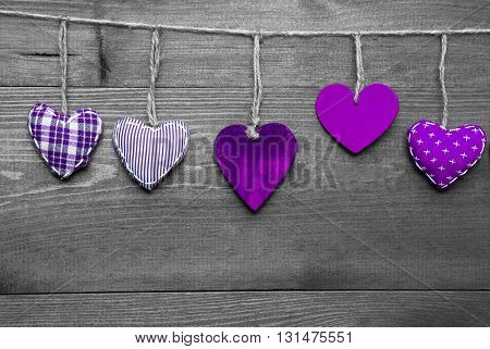 wooden background with purple hearts hanging in a row. black and white style with colored hot spots. copy space for advertisement or free text. greeting card for valentines or mothers day