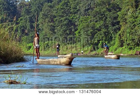CHITWAN, NEPAL - OCTOBER 15, 2008: Local man traveling by rowboat at wild river in Chitwan National Park, Nepal. Park was established in 1973 and granted the status of a World Heritage Site in 1984