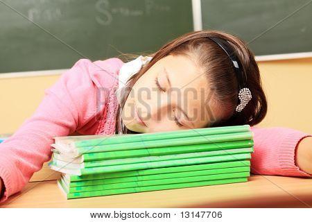 Tema educativo: colegiala durmiendo en sus libros de texto en un aula.