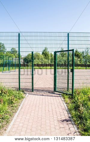 entrance to the playground of fence and the wicket of the welded wire mesh green color with a metal lock and handle