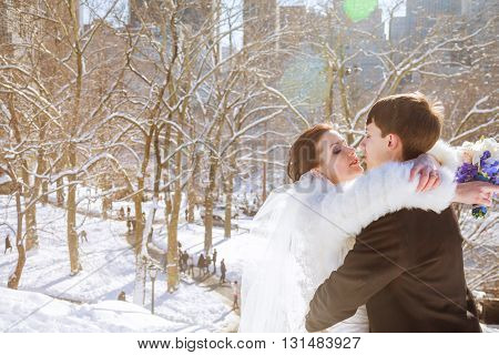 Groom kisses a bride holding her arms while standing in the winter forest
