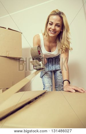 Young girl moving in a new appartmentstanding surrounded with cardboard boxes packing and taping boxes