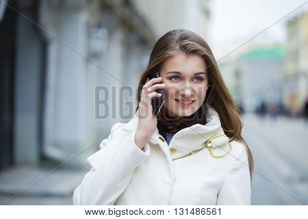Portrait of happy young brunette girl in white coat talking on the phone outdoors spring