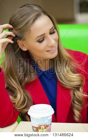 Portrait close up of young beautiful happy blonde woman sitting in a coffee shop