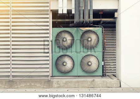 Air compressor machine on pedestal outside building.
