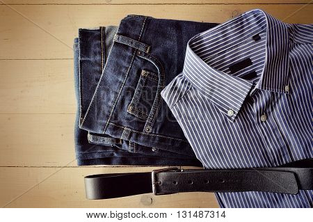 Men's jeans shirt and belt decomposed on a wooden background