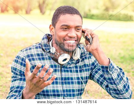 African american man talking on phone with gesture outside - Young university student guy with positive attitude using mobile in city park - Concept of communication with modern electronic devices