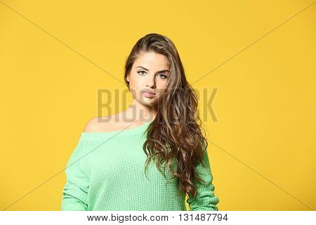 Pretty young woman in green pullover on yellow background