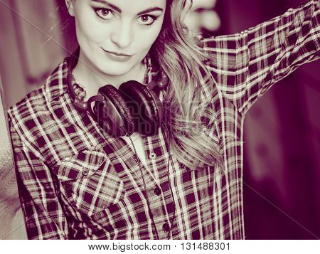 Hobby music style and free time. Young girl with headphones stand indoor wear fashionable clothes.