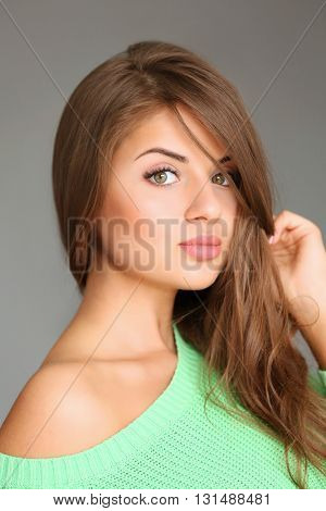Long-haired pretty woman on gray background