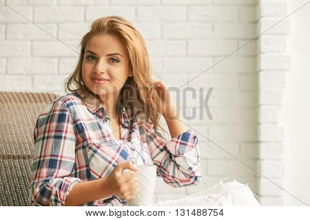 Beautiful young woman holding cup on brick wall background